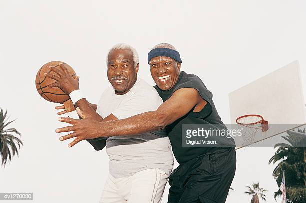 two elderly men playing basketball - muñequera fotografías e imágenes de stock