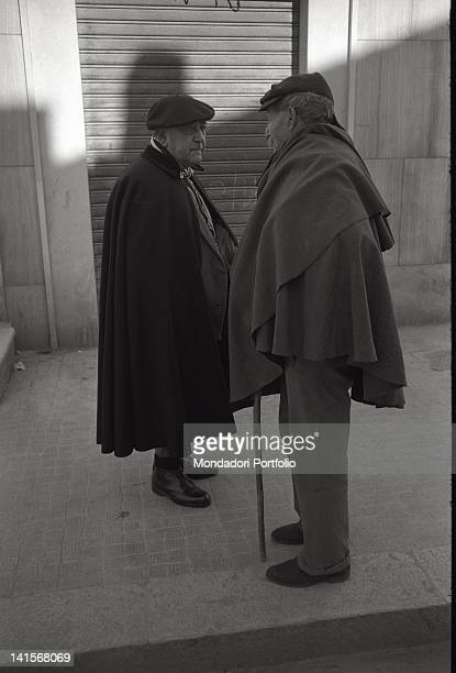 Two elderly men wearing cloaks stop to talk on the pavement beside a road in San Giovanni Rotondo Italy