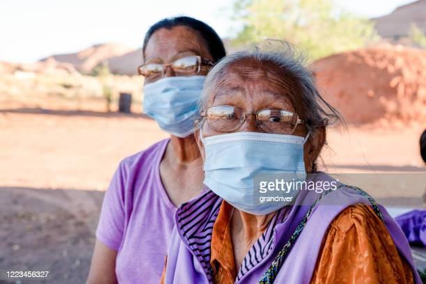 コロナウイルスを手に入れるのを防ぐためにフェイスマスクを着用した2人の高齢のナバホ女性 - ナバホ文化 ストックフォトと画像