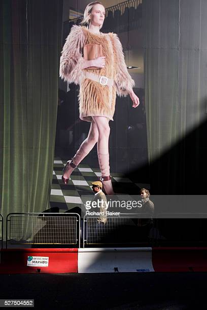 Two elderly pedestrians pass beneath a giant billboard featuring a catwalk model wearing haute couture In London's New Bond Street a road famed for...