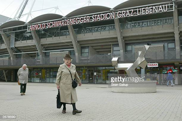 Two elderly people walk past the soccer stadium named after Arnold Schwarzenegger October 10 2003 in Graz Austria Schwarzenegger was born in nearby...