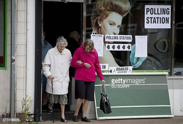 Two elderly voters leave the Ush Hair hairdressing salon which is being used as a polling station in Hull Northern England on May 7 2015 as Britain...