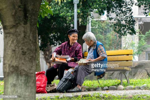 Two elderly women sit on a roadside bench chatting about the junk cardboard they picked this day Picking up and selling junk cardboard is a kind of...