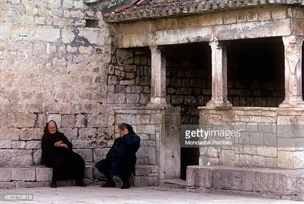 Two elderly women sitting beside the Fishmarket Loggia Trogir 1969