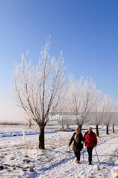 two elderly women walking in a winter landscape
