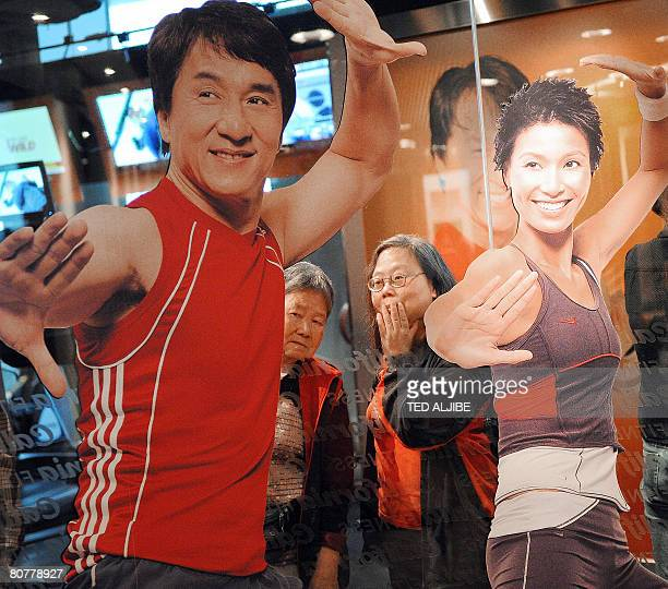 Two elderly women watch customers next to a giant poster of Hong kong action star Jackie Chan during the opening ceremony of a fitness center in Hong...
