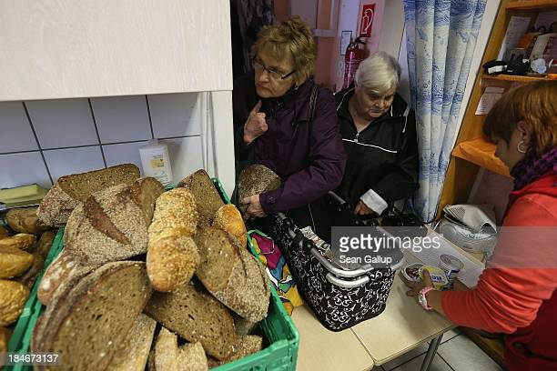 Two elderly women who said they did not mind being photographed purchase groceries at the Falkenseer Tafel food bank on October 15 2013 in Falkensee...