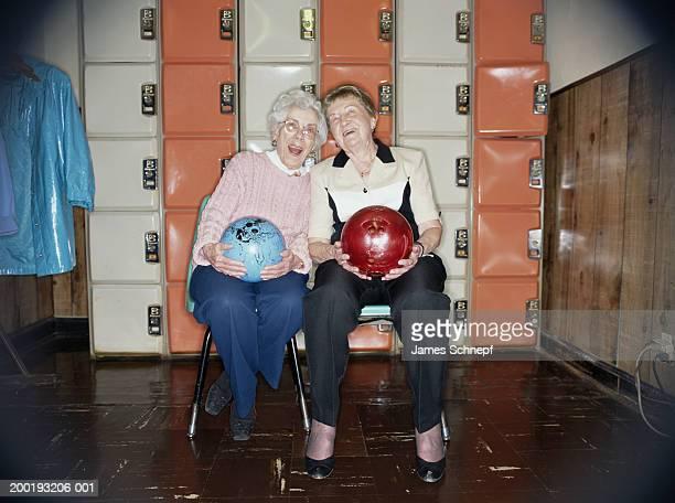 Two elderly women with bowling balls in locker room, smiling, portrait