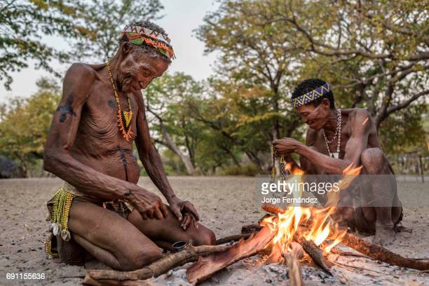 Two elders of the San tribe getting ready for a traditional dance around the fire