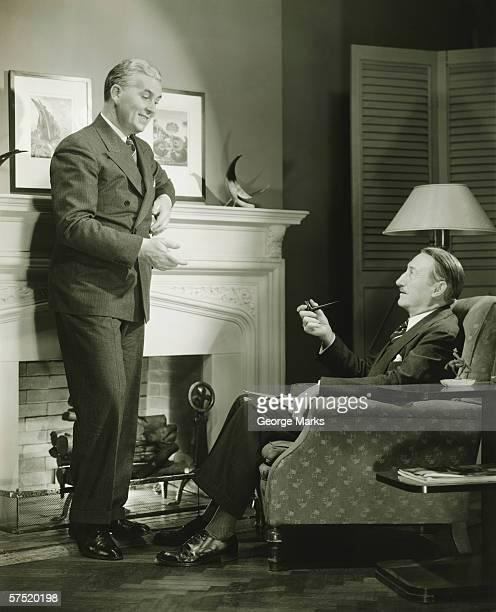 Two elegant men talking by fireplace, (B&W)