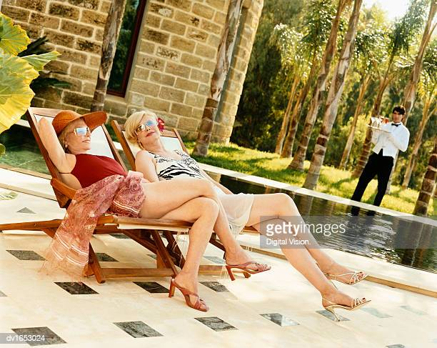 Two Elegant Senior Women in Swimsuits Sit 0n Deckchairs Relaxing By a Pool, Their Butler in the Background