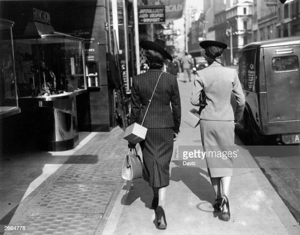 Two elegant women shoppers in Bond street, London carry gas masks in cardboard boxes slung over their shoulders.