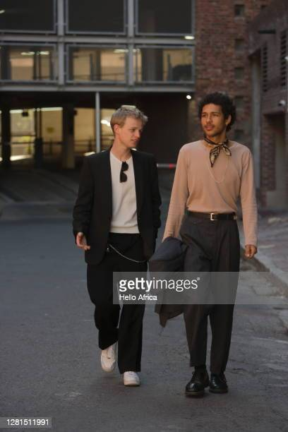 two elegant young men strolling up a street - menswear stock pictures, royalty-free photos & images