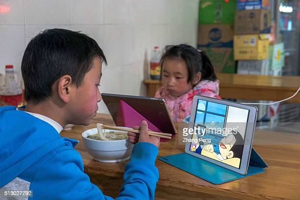 Two elementary school students watch cartoon video and play games on mobile device when having dinner It is always a hot issue whether playing with...