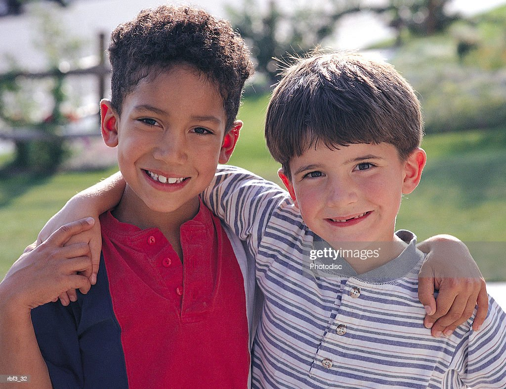 two elementary school-aged boys with their arms around each other smile while standing in a park : Stockfoto