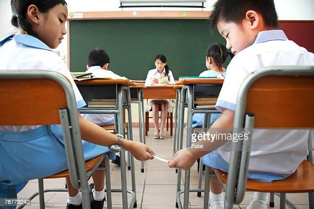 two elementary students passing notes in class - passeren stockfoto's en -beelden