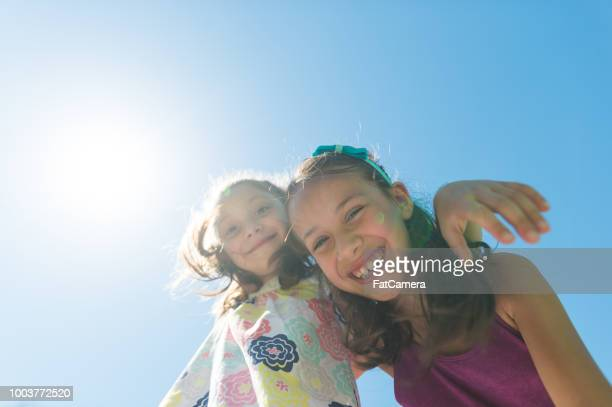 Two elementary-age girls posing together at the park on a sunny day