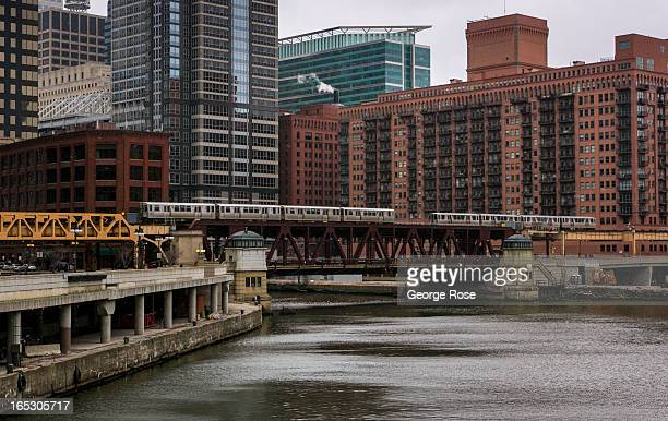 Two elevated trains pass each other as they cross the Chicago River on March 25 2013 in Chicago Illinois Visitors to the Windy City the third most...