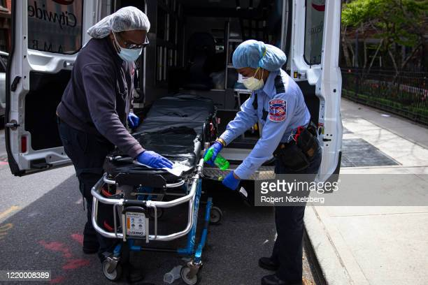 Two emergency medical staff of a private ambulance company sanitize a hospital gurney after they dropped off a patient at the Cobble Hill Health...