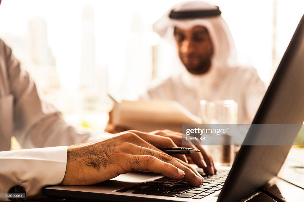 Due Emirates business uomo riempiendo documenti in una caffetteria : Foto stock