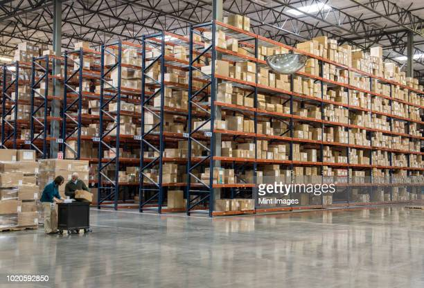 two employees checking inventory beside racks of boxes in temporary storage in a distribution warehouse. - 倉庫 ストックフォトと画像