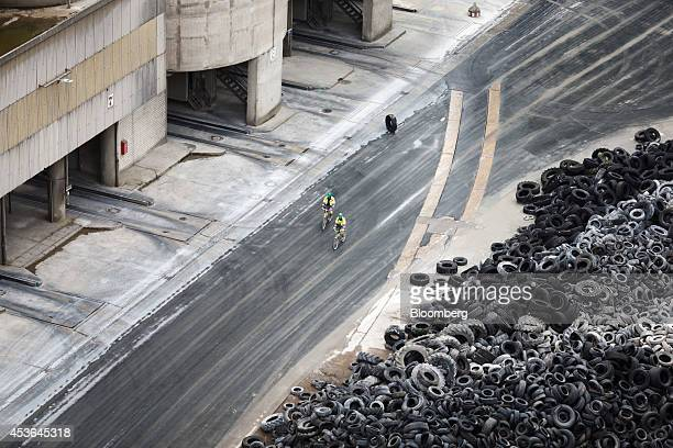 Two employees cycle past a mound of rubber vehicle tires used to fuel the cement factory at HeidelbergCement AG's plant in Ennigerloh Germany on...