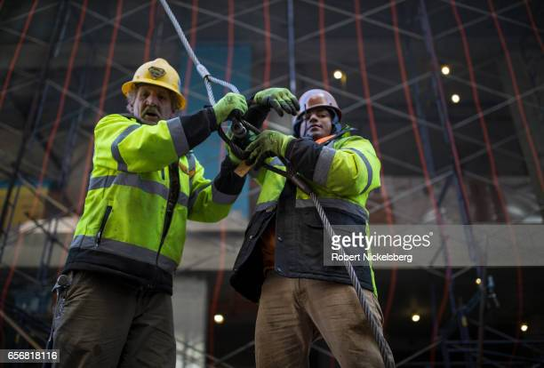 Two employees of a crane company secure cables to a delivery of steel reinforcement bars March 20 2017 at a midtown building site in New York City...