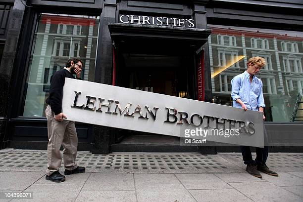 Two employees of Christie's auction house manoeuvre the Lehman Brothers corporate logo, which is estimated to sell for 3000 GBP and is featured in...