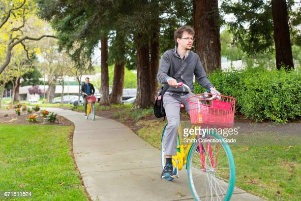 Two employees of Google Inc known colloquially as Googlers ride colorful Google Bikes at the Googleplex headquarters of Google Inc in the Silicon...