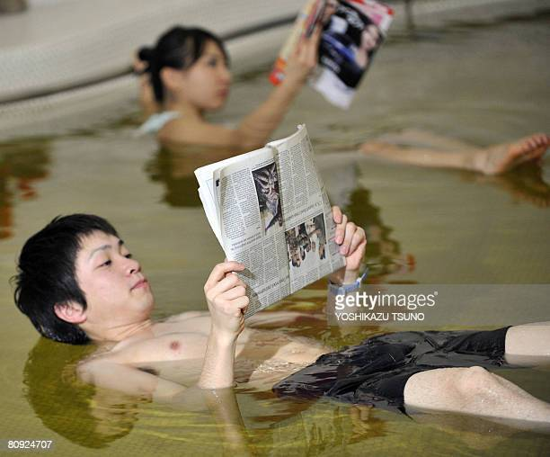 Two employees of Japan's spa resort 'Yunessun' read a magazine and a newspaper as they float during a demonstration in the Dead Sea spa which has...