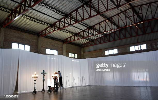 Two employees of the burial house set up chandeliers at San Martin Club gymnasium ahead of Emiliano Sala's funeral on February 15 2019 in Progreso...