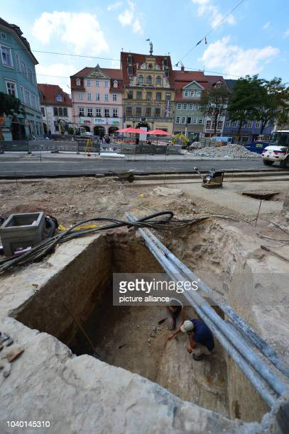 Two employees of the Office for Listed Buildings work on the floor of the historical city hall tower from 1330 in Erfurt Germany 05 August 2013 The...
