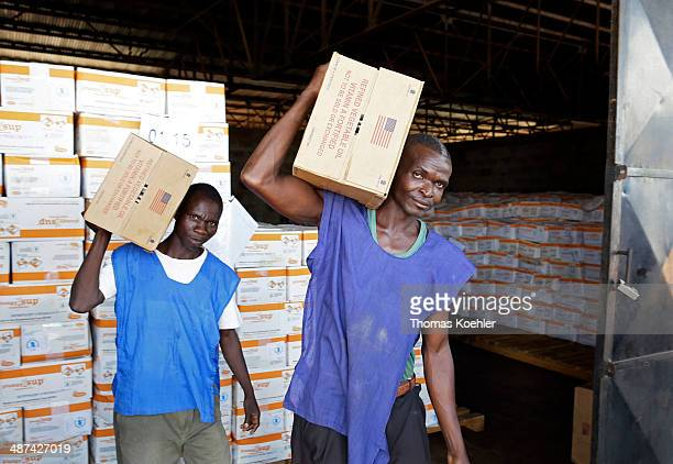 Two employees of the World Food Programme WFP carrying boxes of basic foodstuffs at a logistics center as pictured on March 14 2014 in Bangui Central...