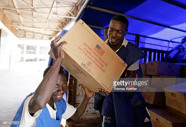 Two employees of the World Food Programme WFP loading boxes of basic foodstuffs at a logistics center as pictured on March 14 2014 in Bangui Central...