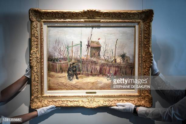 """Two employees put on display a painting titled """"Scene de rue a Montmartre"""" , 1887 by Dutch painter Vincent Van Gogh, at the Sotheby's auction house..."""