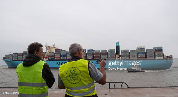 Two employees watch the world's biggest container ship the Maersk MCKinney Moller as it arrives at the port of Bremerhaven on August 18 2013 in...