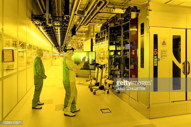 Two employees work in a clean room of the semiconductor Bosch factory during preparations for the series production of semiconductor chips on...