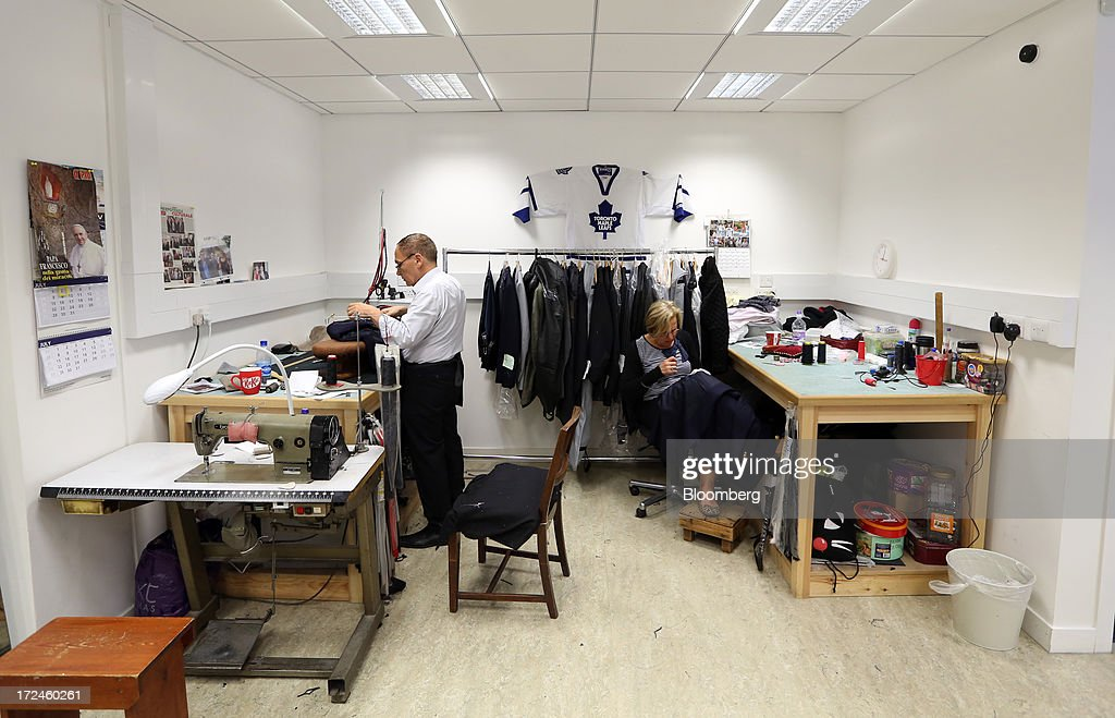 Two employees work on the manufacture of suits in the workshop of the tailors Dege & Skinner based on Savile Row in London, U.K., on Tuesday, July 2, 2013. New orders at manufacturers rose for a fourth month in June, led by the textiles clothing industry, while input costs fell for a third month. Photographer: Chris Ratcliffe/Bloomberg via Getty Images