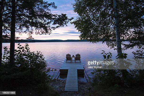 Two empty adirondack Chairs sitting on a dock on a Spencer Pond in northern Maine.