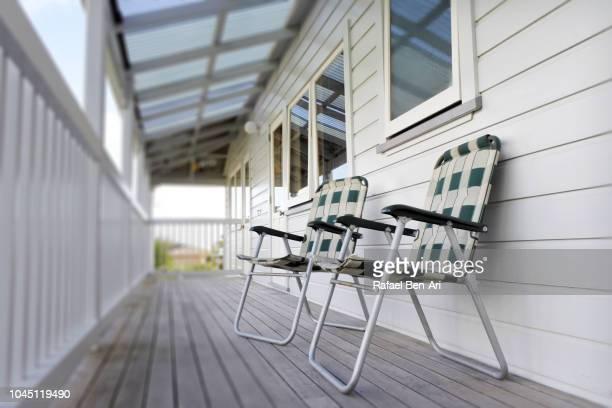 two empty chairs on home balcony - rafael ben ari stock-fotos und bilder