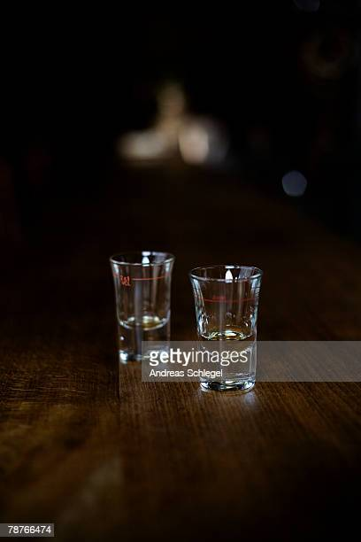Two empty shot glasses on a bar