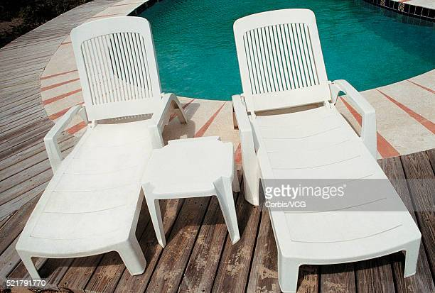 Two empty sun loungers besides swimming pool