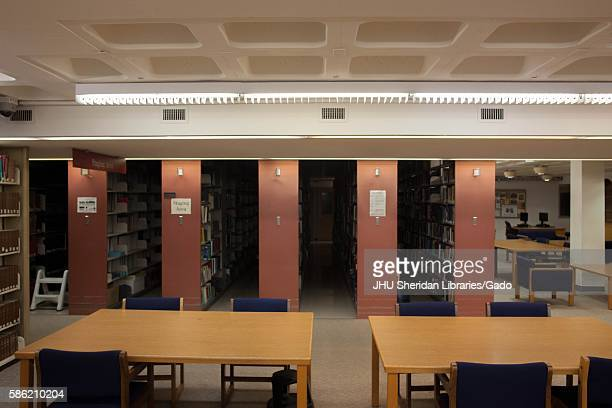 Two empty tables in a library with red stacks behind the tables, 2014. Courtesy Eric Chen. .