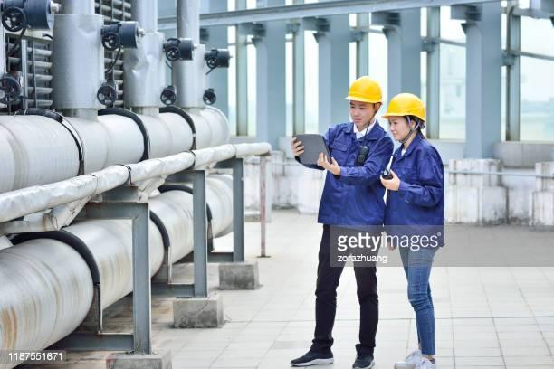 two engineer colleagues examining cooling tower equipment - estação de tratamento de esgotos imagens e fotografias de stock