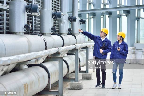 two engineer colleagues examining cooling tower equipment - sewer stock pictures, royalty-free photos & images