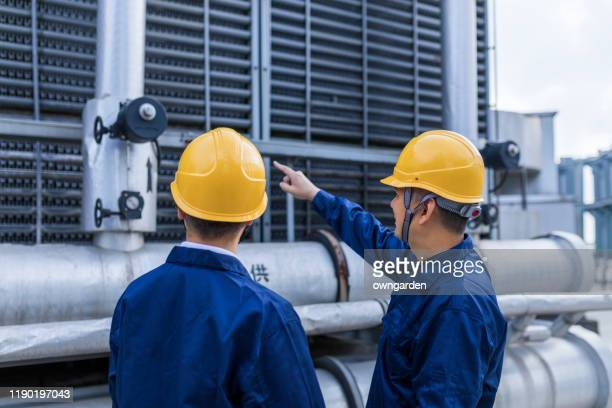 two engineer colleagues examining cooling tower equipment - cooling tower stock pictures, royalty-free photos & images