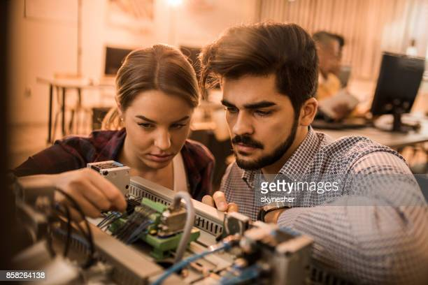 Two engineering students working on electrical component of a machine in laboratory.