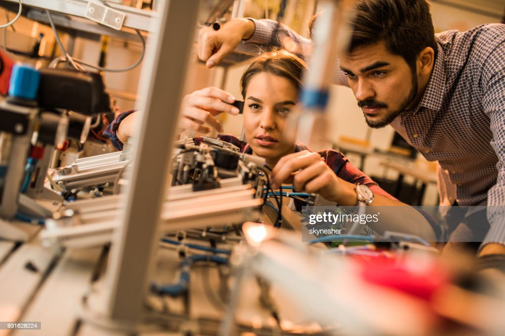 Two engineering students working on electrical component of a machine in laboratory. : Stock Photo