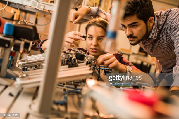 two engineering students working on electrical component of a machine in laboratory. - electronics stock pictures, royalty-free photos & images