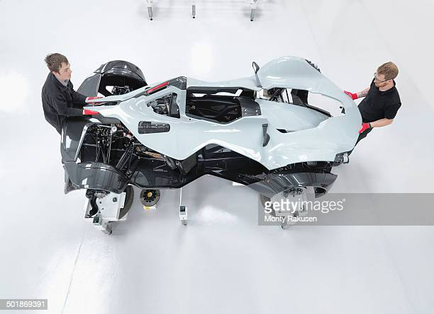 Two engineers assembling supercar in sports car factory, overhead view